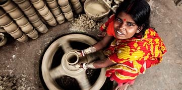 Woman throws clay pot on a pottery wheel in Bangladesh. Photo by Mohammad Reaz Uddin, CGAP Photo Contest