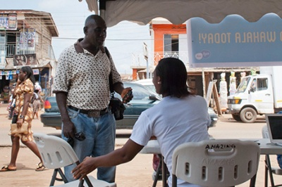 Woman holds chair out, offering good customer service to a low-income customer at a prototype financial services business in Accra, Ghana