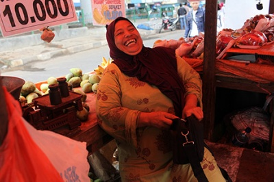 Entrepreneur laughs in her place of business - a fruit stall. Low-income earners like this woman require financial services tailored to their business and personal financial needs – and delivered in a user-friendly, customer-centric approach.