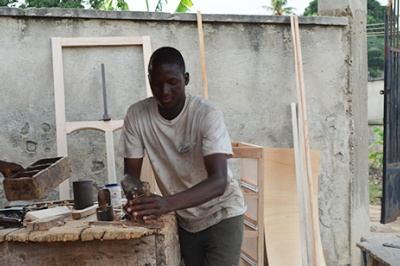 Carpenter saws wood in Kumasi, Ghana. Low-income individuals like this man seek financial predictability and reliable income but may face challenges and risks that prevent them from achieving these goals