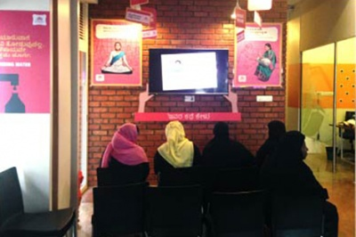 Low-income women customers at a bank branch in Pakistan look at a prototype created through customer experience insights work