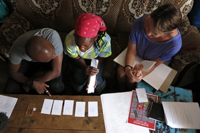 Low-income woman in Kenya looks at papers on table during a one-on-one customer insights qualitative research interview in her home.