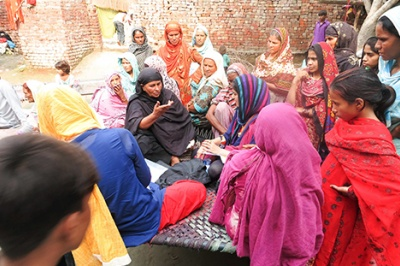 Women in Pakistan gather in a group to discuss financial habits, needs, and challenges with using formal financial services.