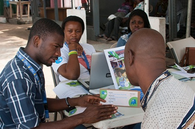 Tito Cash representative teaches a mobile money user in Ghana about USSD long codes, providing positive customer service to a customer in a low-income segments