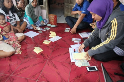 Low-income women in Indonesia look at and discuss their microcredit group loan documents