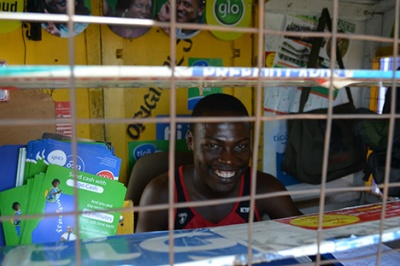A smiling mobile money agent in Ghana provides good customer experience and a customer-centric attitude at his Tigo Cash booth
