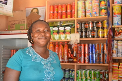 Woman entrepreneur with a shop full of stocked shelves is ready to offer good customer experience to low-income customers, Zambia