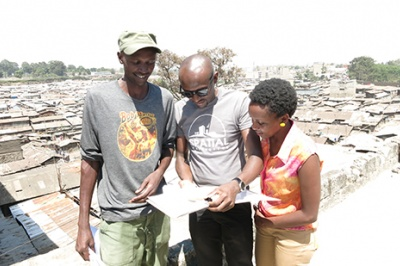 During a qualitative research interview in Kibera, Kenya, three people look at paper