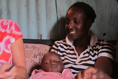 Low-income woman in Kenya smiles and holds baby during a qualitative interview in her home.
