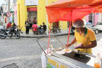 Woman at her street cart. Low-income entrepreneurs like this woman benefit from financial services that offer improved customer experience.