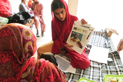 Woman in Pakistan holds a paper as she tests a financial services prototype designed to bring more user-friendly products and services to low-income customers.