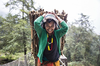 Woman smiles as she carries wood. Low-income customers and those with less stable income flows like this woman in rural Nepal benefit from financial services and products that suit their needs and behaviors, and make formal financial services more accessible and intuitive for low-income segments.