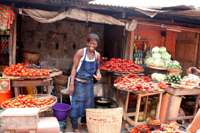 Woman entrepreneur in her vegetable stall provides customer-centric service to her customers.