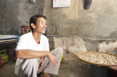 Indonesian man with big pot is interviewed to identify business opportunities to serve low-income customers with customer-centric products and services.