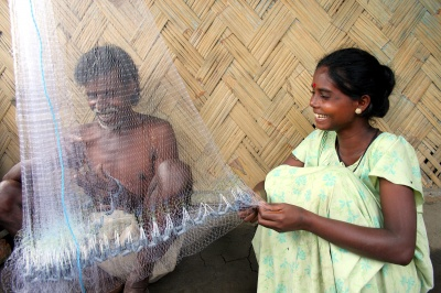 low-income man and woman repair fishing nets, a daily task for small business entrepreneurs.