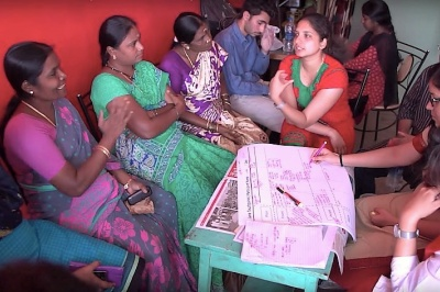 Janalakshmi customers interact with staff at a Janalakshmi branch of the small bank, India.